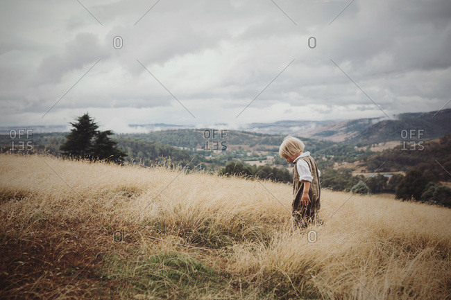 Young blonde girl hikes through the wild grass on top of a hill wearing linen overalls.