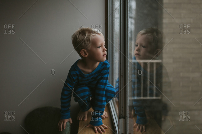 Young blonde boy looks out of window on a cold morning in his pyjamas looking curious.