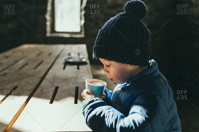Boy blows on hot chocolate to cool it down wearing a beanie and puffer jacket and sitting in a hut.