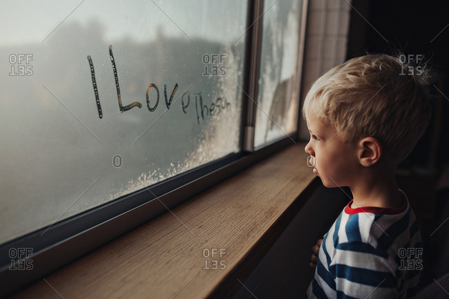 """Boy stares out of foggy window with the words """"I Love The Sun"""" wearing his striped pyjamas."""