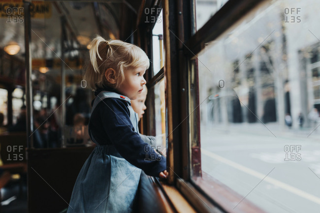 Young blonde girl stares out of the window of a tram in the city of Melbourne Australia.
