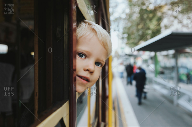 Young blonde boy looks out of tram window as it's travelling through the city of Melbourne Australia.