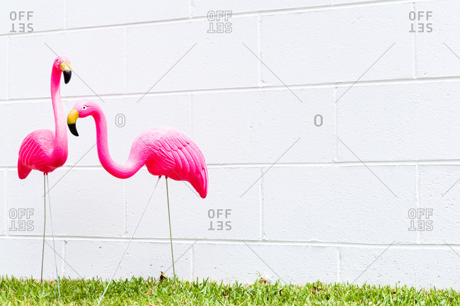 Two pink flamingo decorations in yard