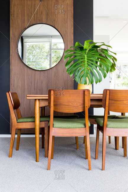 Dining room with modern dining table, potted plant, and round mirror hanging on wall