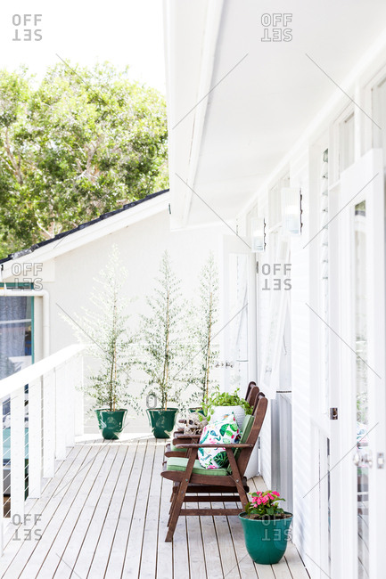 White wooden deck with patio chairs outside home
