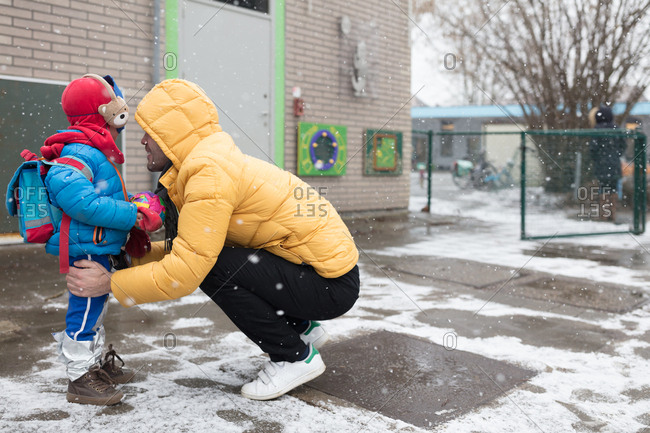 Happy father greeting kid at the school gates in winter