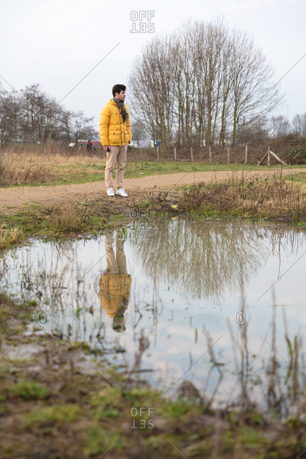 Man with scarf standing by puddle of water in nature