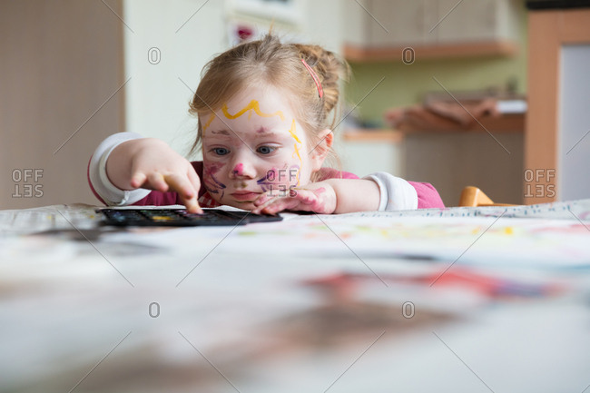 Girl painting with fingers at home