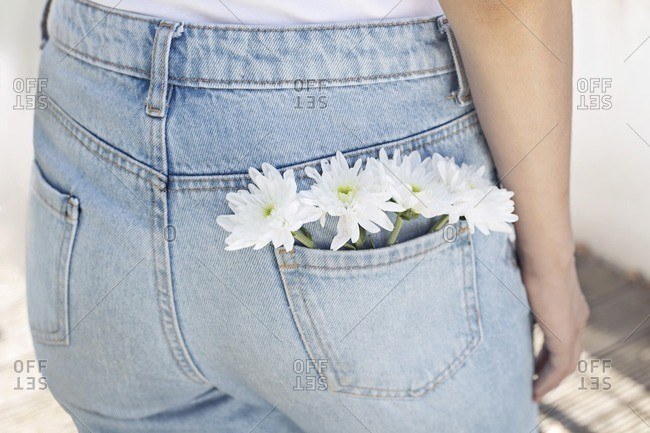 Woman with white flowers in back pocket of her jeans.