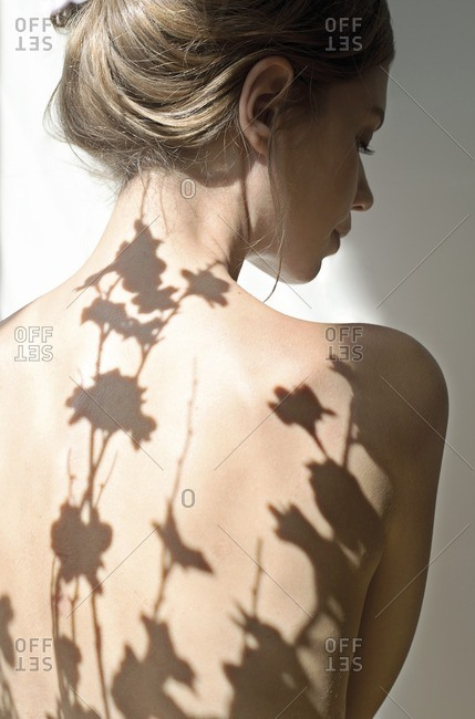 Woman with shadows of plants on her back.