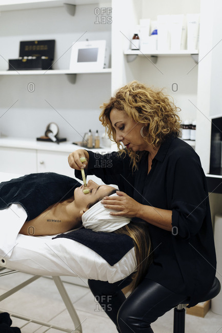 Spa technician using stone roller on woman's face during spa session