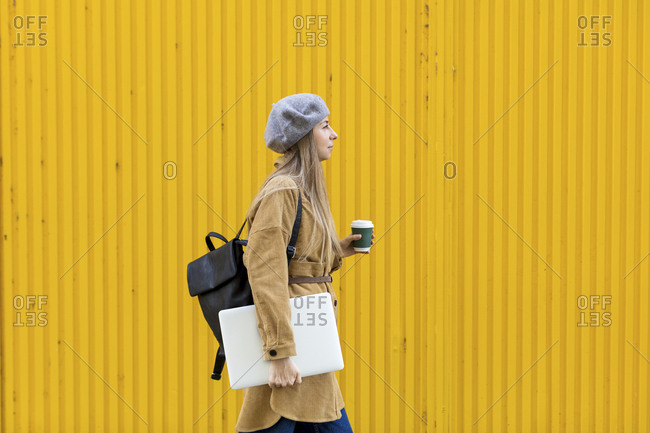 Woman walking with coffee and laptop