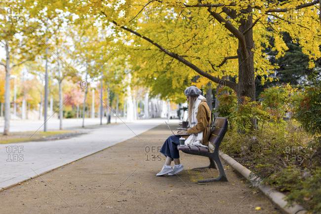 Woman sitting on park bench with coffee and laptop