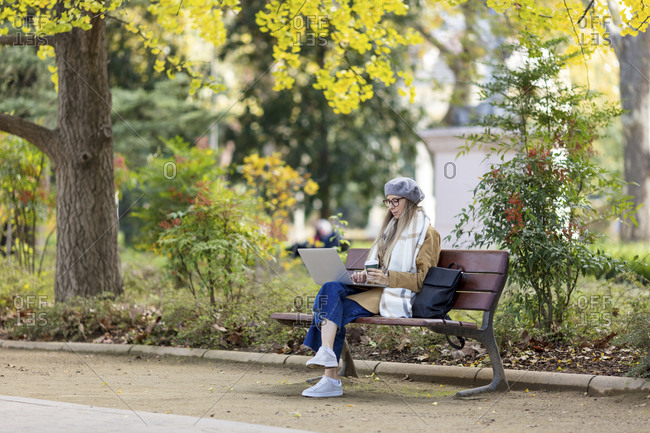 Woman sitting on park bench with coffee using laptop