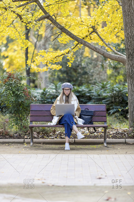 Blonde woman sitting on park bench with coffee using laptop