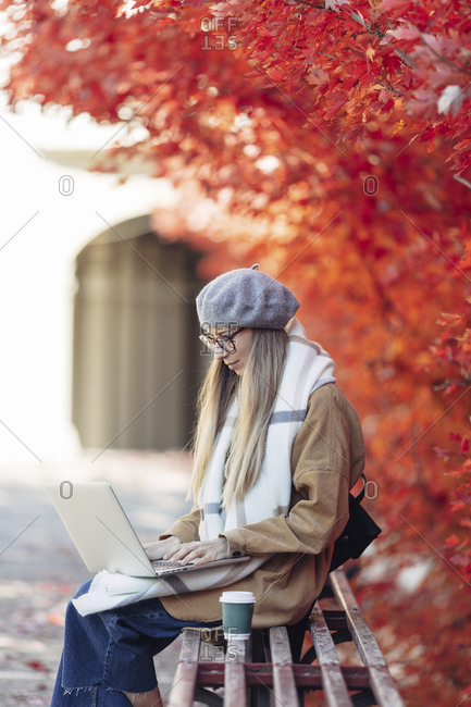Woman sitting on bench in a park with coffee and laptop