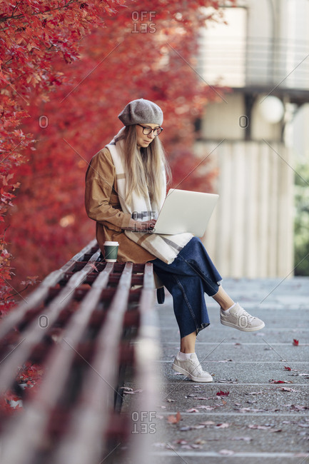 Blonde woman sitting on bench in a park with coffee and laptop