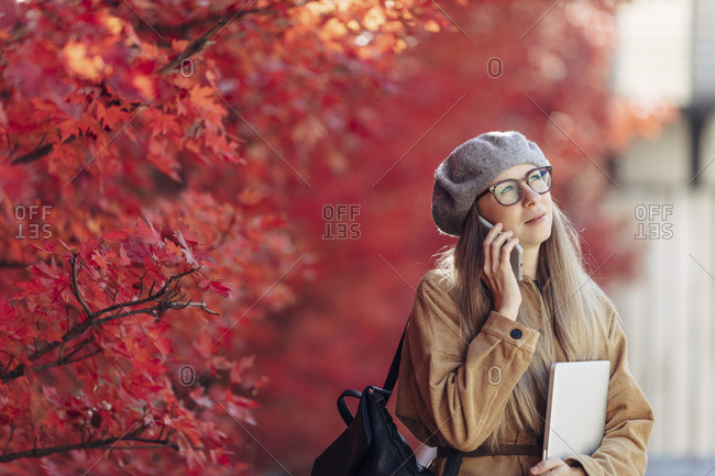 Blonde woman in a park talking on phone