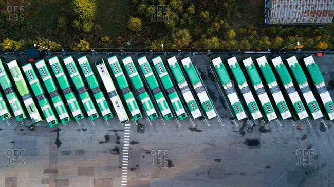 Aerial view of green busses in a parking lot