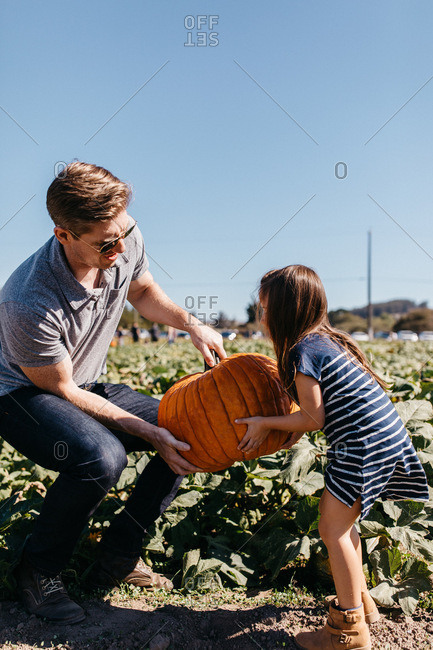 Father helping daughter lift pumpkin at the pumpkin patch