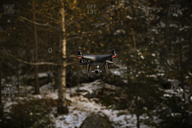 Drone with camera flying with a forest in the background