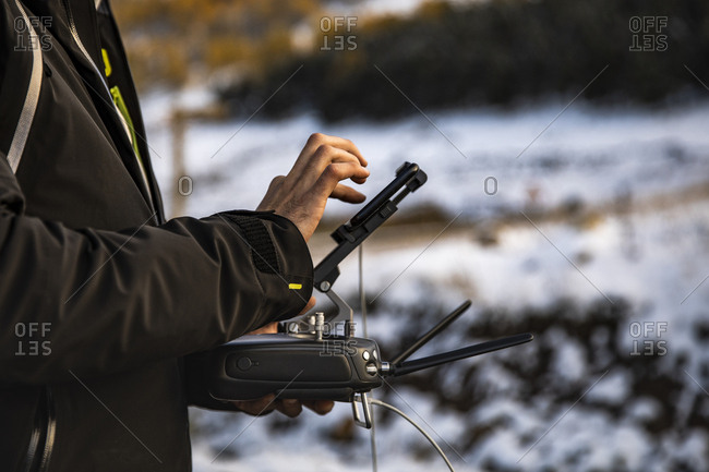 Photo detail of the hands of a man in the control of the drone with a snowed forest in the background