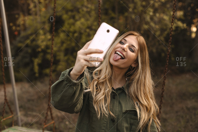 Pretty blonde teen doing a selfie with the phone sitting on a swing in nature