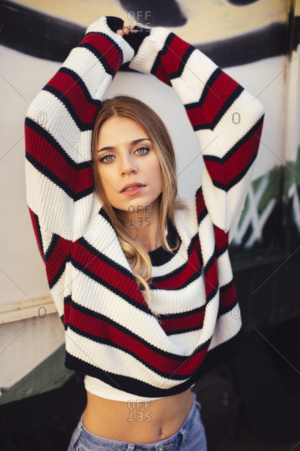 Portrait of a pretty blonde girl with striped shirt with graffiti background
