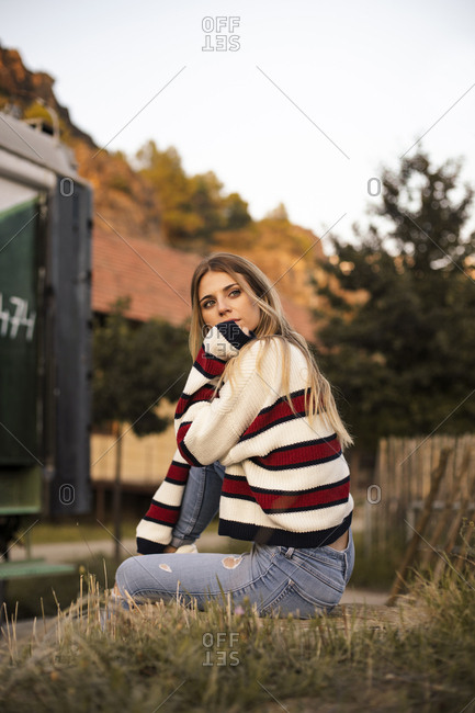 Portrait of a pretty blonde girl sitting with striped shirt in nature