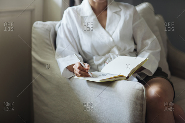 Unrecognisable woman sitting in armchair writing in her notebook.