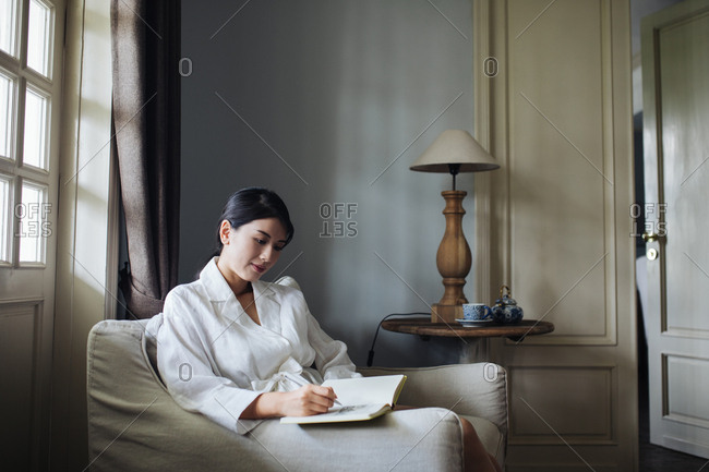 Beautiful Thai woman sitting on a armchair and writing in her notebook.