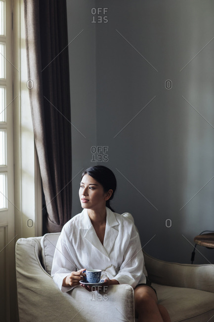 Portrait of beautiful Asian woman enjoying sitting on armchair and holding a cup of tea.
