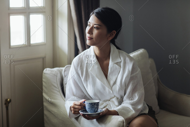 Portrait of beautiful Thai woman enjoying sitting on armchair and holding a cup of tea.