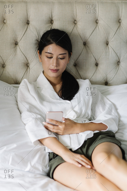 Beautiful Thai woman sitting on a king-size cozy bed and using her cell phone.