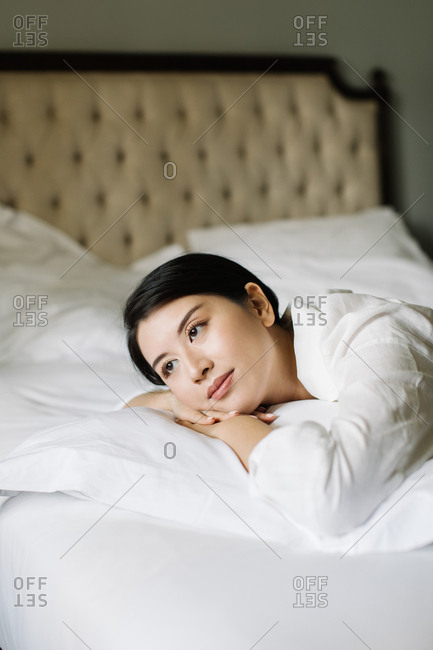 Portrait of beautiful Asian woman enjoying lying on a bed.