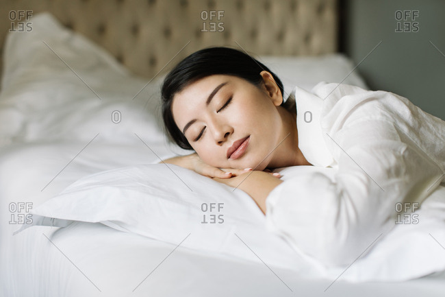 Beautiful Thai woman sleeping on a king-size bed.
