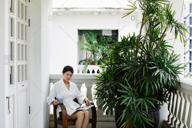 Beautiful Asian woman sitting on a terrace and reading a magazine and drinking tea.