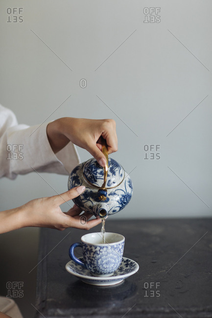 Hands of unrecognizable woman pouring a tea from porcelain carafe.