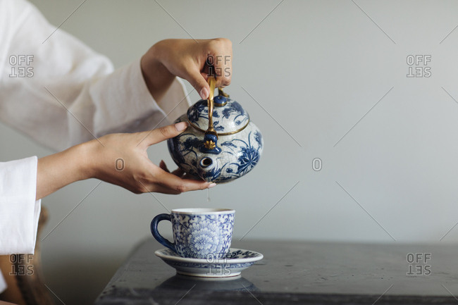 Hands of unrecognizable woman pouring a tea from ceramic carafe.