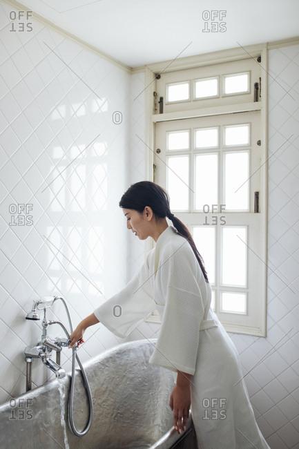 Beautiful Asian woman wearing bathrobe using a faucet at bathroom.