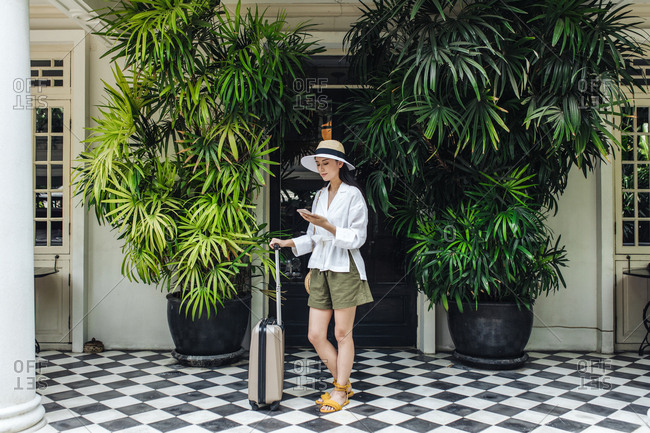 Beautiful Asian woman vacationer standing in front of a hotel with a suitcase and holding her cell phone.