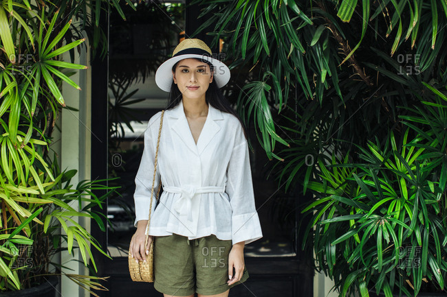 Portrait of pretty Asian woman wearing a hat and linen shirt and shorts standing outdoors and looking at camera.