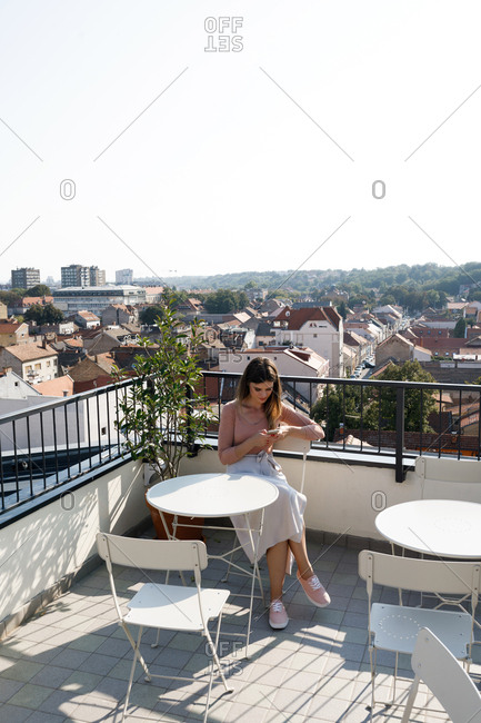 Beautiful Caucasian woman sitting on rooftop and typing on her smart phone.