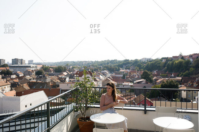 Beautiful Caucasian woman sitting on rooftop and enjoying the sunny day.