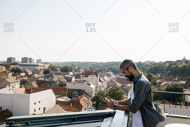 Smiling Casual man standing on rooftop terrace and typing on his smart phone.