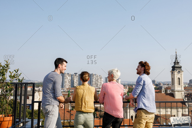 Group of friends standing on rooftop terrace and enjoying the view.