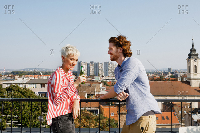 Pretty Caucasian woman and smiling man enjoying sunny day on a rooftop terrace.