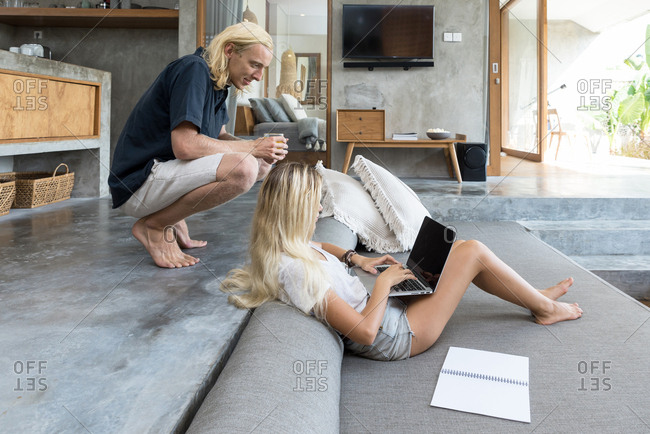 Couple on sofa with laptop computer in luxury villa