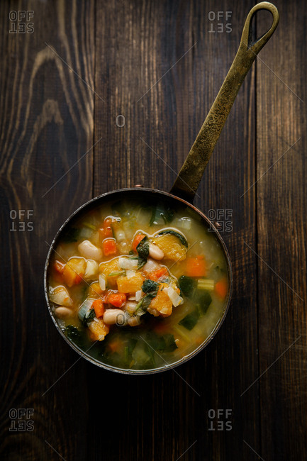 Zuppa Frantoiana - italian bean soup with pumpkin and vegetables in a copper saucepan