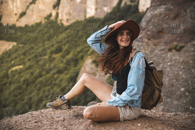 Smiling young woman on a hiking trip wearing a hat sitting on a rock